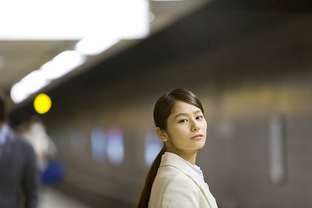 Business woman standing on platform and looking at the camera stock photo