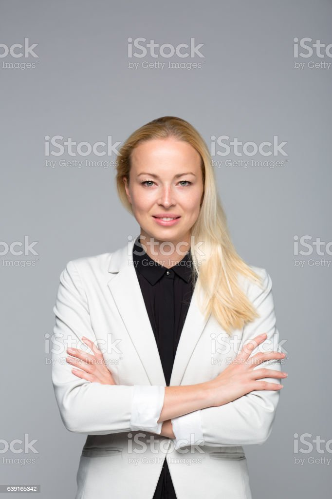 Business woman standing with arms crossed against gray background. Lizenzfreies stock-foto
