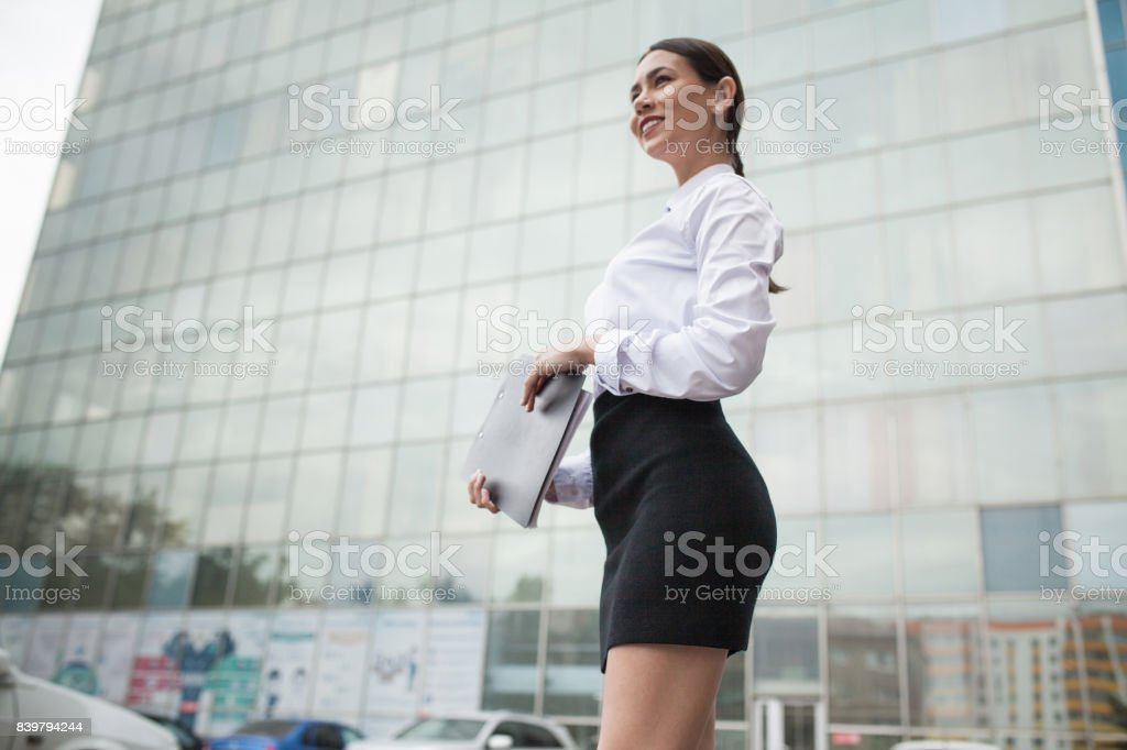 Business woman stands on the background of business center.