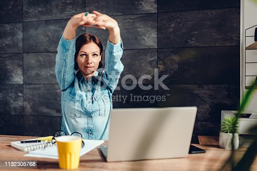 916520034istockphoto Business woman stretching arms in the office 1132305768