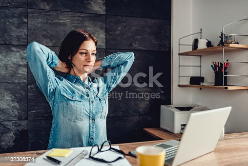 916520034istockphoto Business woman stretching arms in the office 1132308374