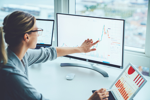 istock Business woman study financial market to calculate possible risks and profits.Female economist accounting money with statistics graphs pointing on screen of computer at desktop. Quotations on exchange 1170740969