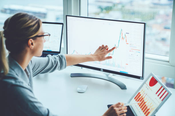 business woman study financial market to calculate possible risks and profits.female economist accounting money with statistics graphs pointing on screen of computer at desktop. quotations on exchange - finance zdjęcia i obrazy z banku zdjęć