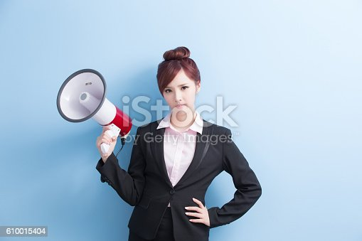 istock business woman take microphone angrily 610015404