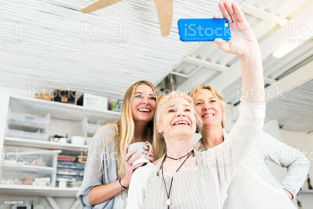 Business woman taking a photo of her team in workshop stock photo
