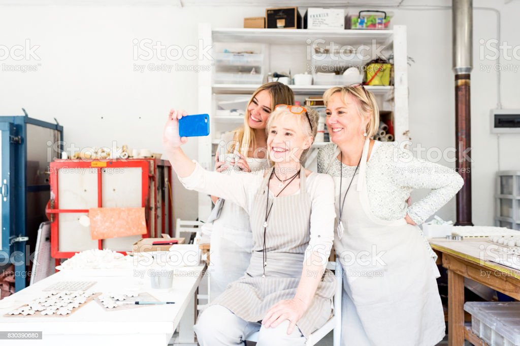 Business woman taking a selfie with her team in workshop stock photo