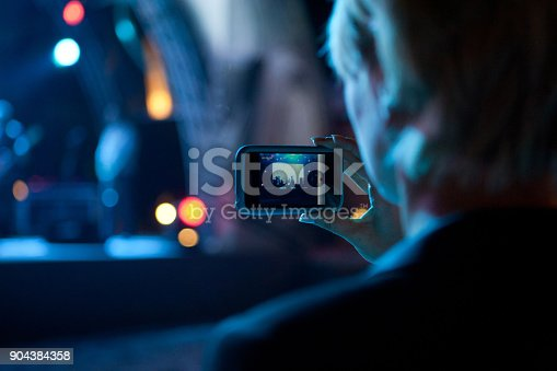 833314292 istock photo Business woman taking photo with cell phone at a concert 904384358