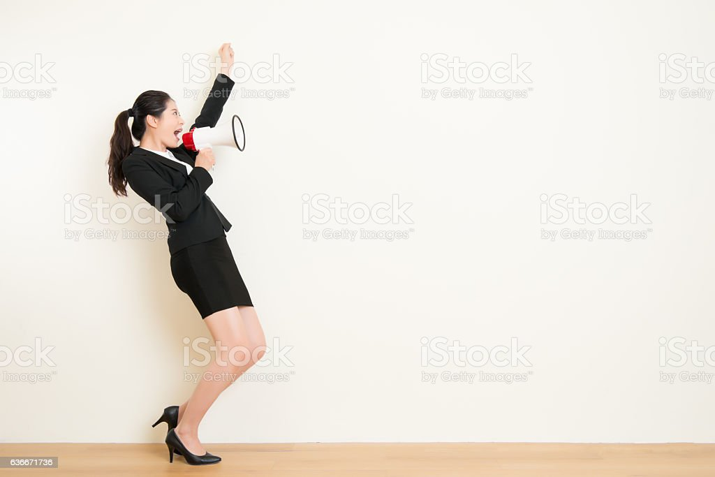 business woman talking in megaphone with white wall - Photo
