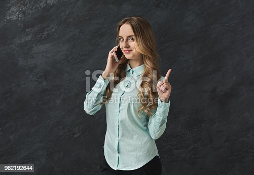 Cheerful business woman talking on phone point be quiet. Young girl having important conversation, showing wait a minute sign with finger, gray studio background, copy space