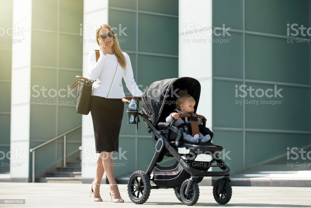 Business woman talking on the phone and pushing baby stroller stock photo