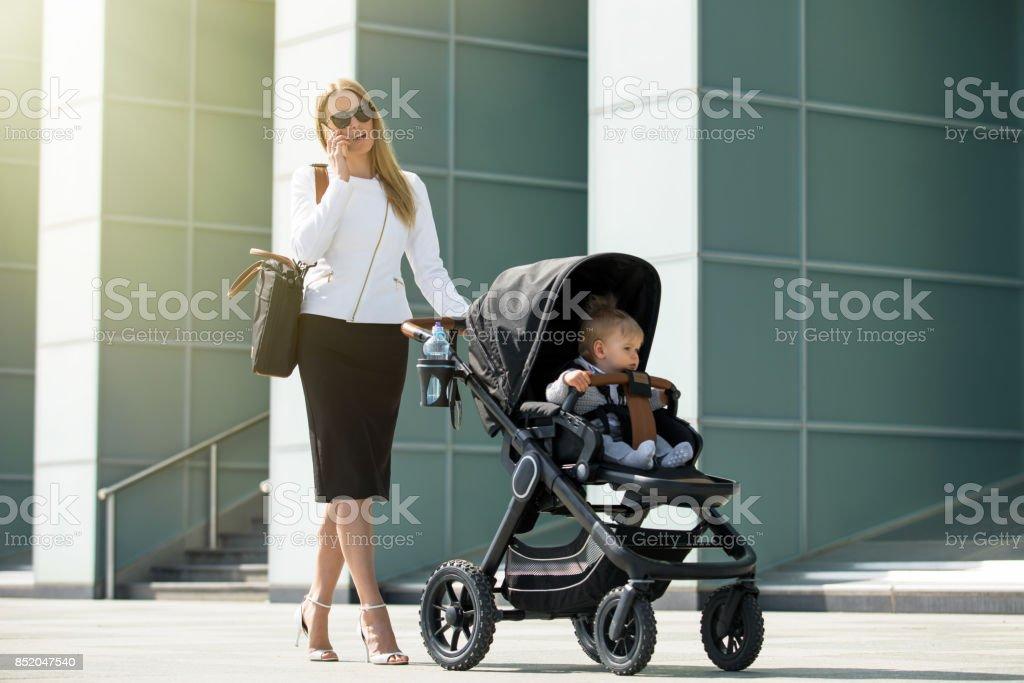 Femme d'affaires parler au téléphone et en poussant la poussette de bébé - Photo