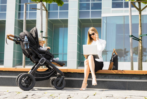 Business woman talking on the phone and working on laptop outdoors while having a baby in stroller stock photo