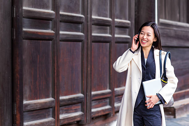 Business woman talking on the phone while walking stock photo