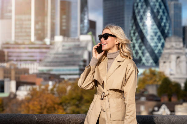 Business woman talks on her mobile phone in front of the skyline of London stock photo