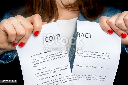 94113879istockphoto Business woman tearing contract - isolated on black 857281242