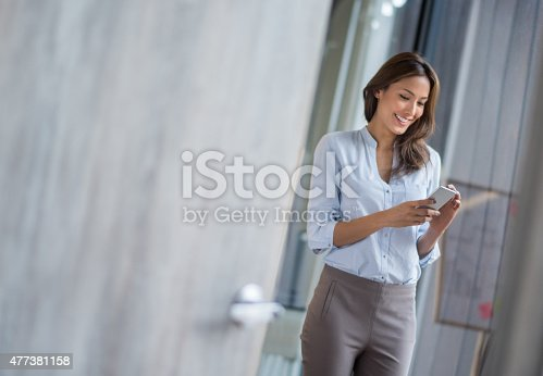 istock Business woman texting on her phone 477381158