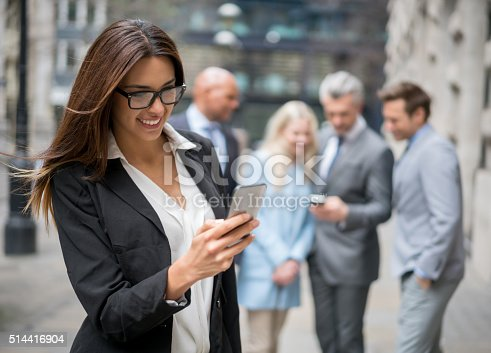 istock Business woman texting on her phone 514416904