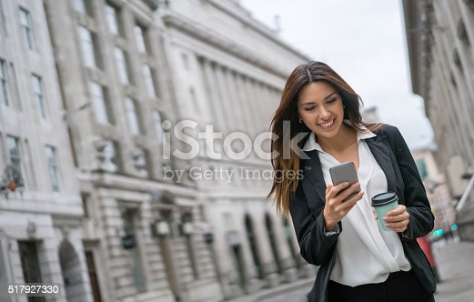 istock Business woman texting on her phone 517927330