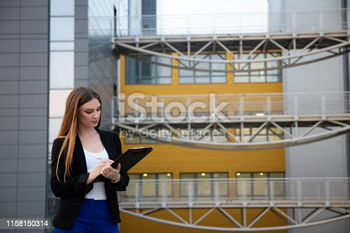 639428672istockphoto Business woman thinking about business plan while standing in front of work place 1158150314