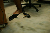 Down view, under the desk of a business woman tired feet without shoes