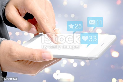 Business woman touching the mobile phone screen with notification of message, likes and important things over blurred light background