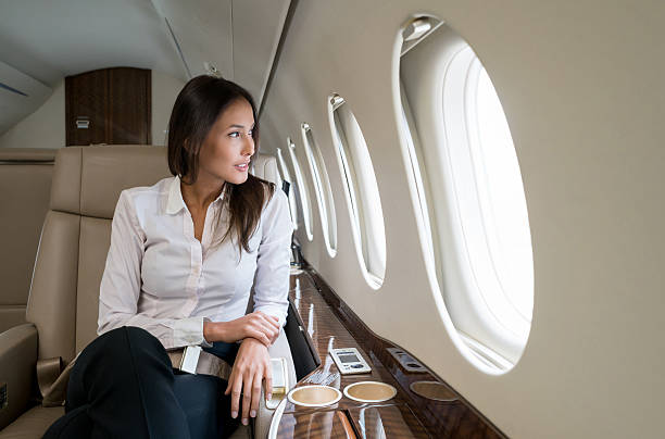 Business woman traveling in a private jet Successful business woman traveling in a private jet and looking happy first class stock pictures, royalty-free photos & images