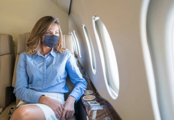 Business woman traveling in a private jet wearing facemask stock photo
