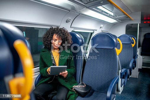 Business woman traveling with train. She is using digital tablet