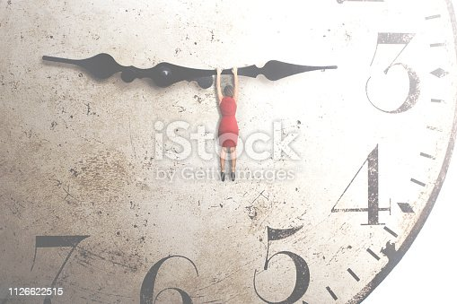 istock business woman trying to stop the time hanging on the hand of a clock 1126622515