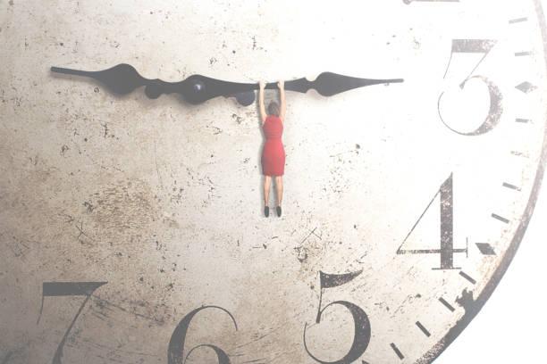 Business-Frau, die versucht, die Zeit an der Hand einer Uhr hängt zu stoppen – Foto