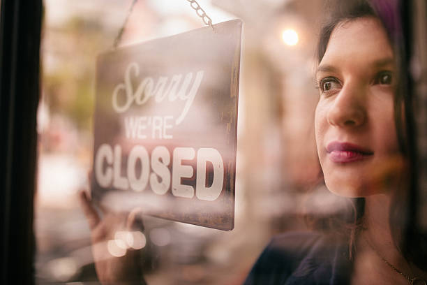 business woman turning closed sign on door of coffee shop - closed stock photos and pictures