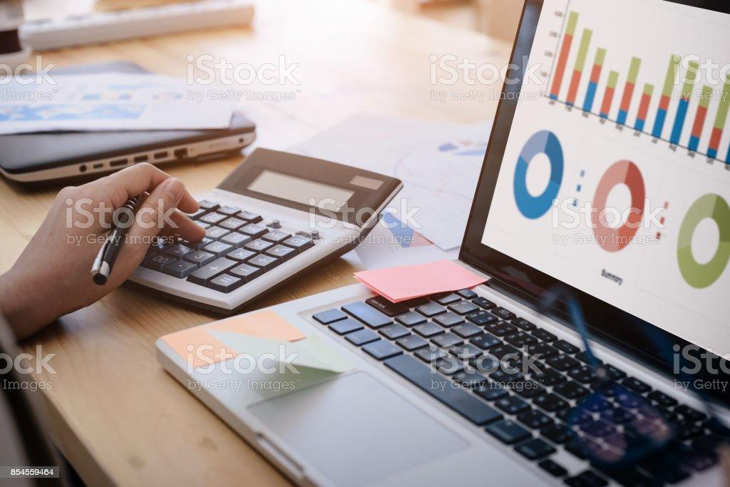 Geschäftsfrau verwendet einen Taschenrechner zur Berechnung des Unternehmens-Performance-zahlen, Grafiken die monatlichen Graphen für die Besprechung. – Foto