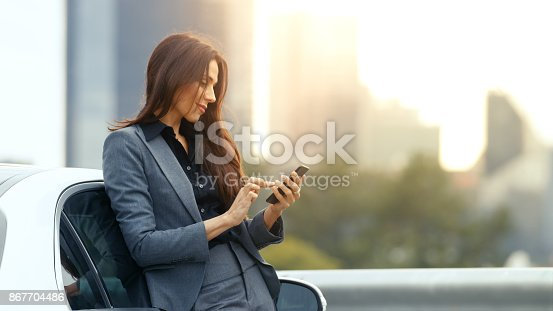 istock Business Woman Uses Smartphone While Leaning on Her Premium Class Car. Big City with Skyscrapers in the Background. 867704486