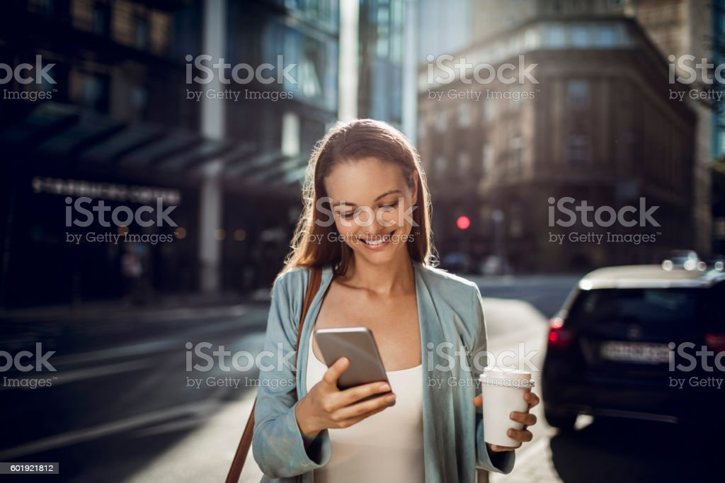 Business woman using a phone while walking - Royalty-free Adult Stock Photo
