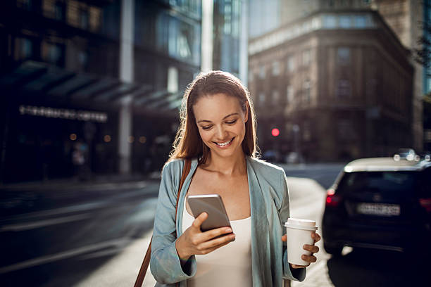 Business woman using a phone while walking stock photo