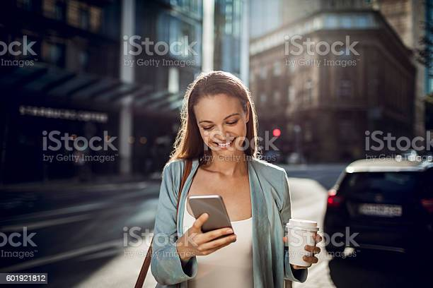Business Woman Using A Phone While Walking Stock Photo - Download Image Now