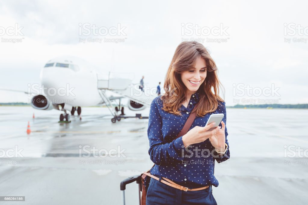 Business woman using a smart phone in front of airplane stock photo