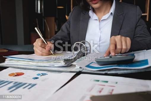 645670208istockphoto Business woman using calculator and laptop for do math finance on wooden desk in office and business working background, tax, accounting, statistics and analytic research concept 1130830024