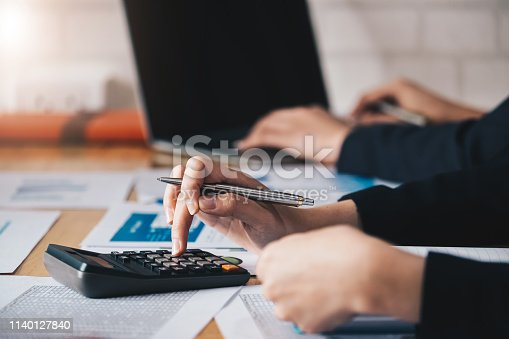 istock Business woman using calculator and laptop for do math finance on wooden desk in office and business working background, tax, accounting, statistics and analytic research concept 1140127840
