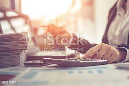 istock Business woman using calculator and writing make note with calculate. Woman working at office with laptop and documents on his desk 930578650
