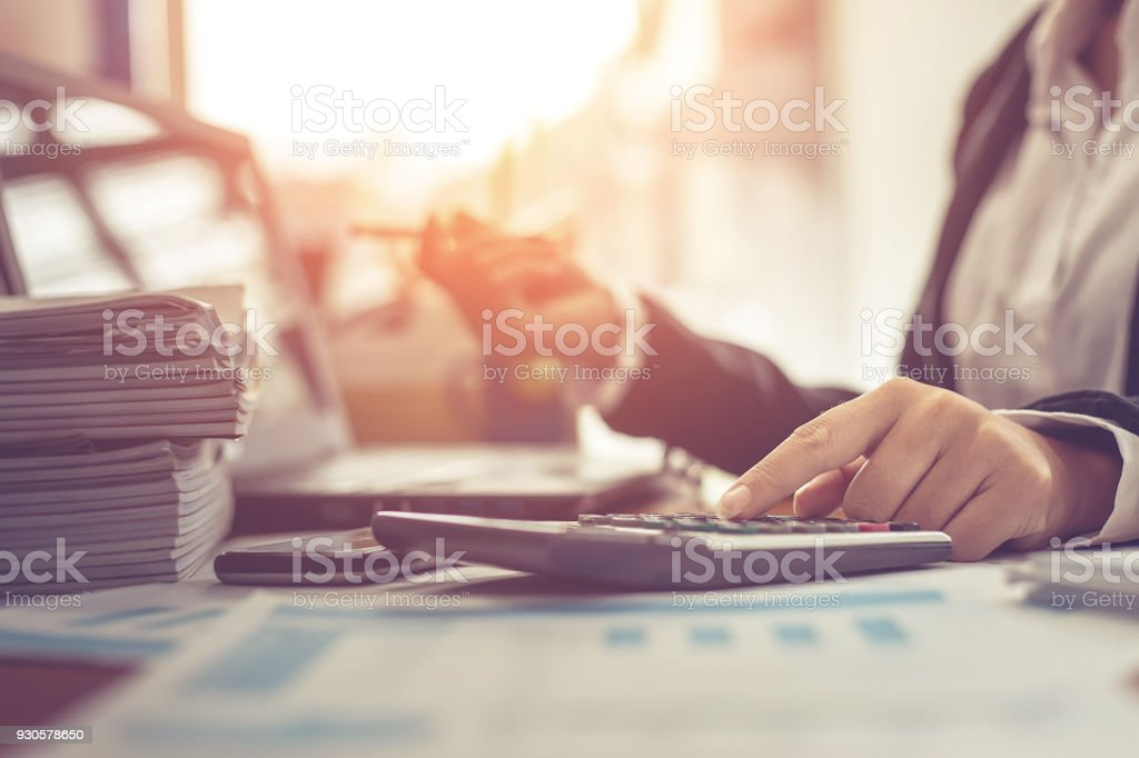 Business woman using calculator and writing make note with calculate. Woman working at office with laptop and documents on his desk stock photo
