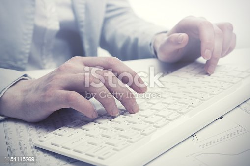 878863400istockphoto Business woman using computer keyboard in office 1154115269