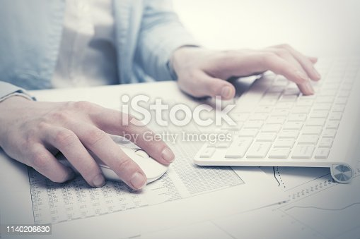 878863400istockphoto Business woman using computer mouse and keyboard 1140206630