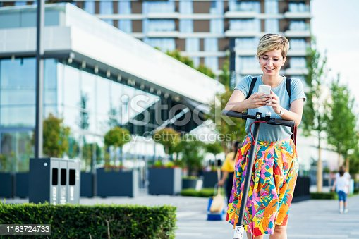 874772840istockphoto Business woman using electric scooter 1163724733