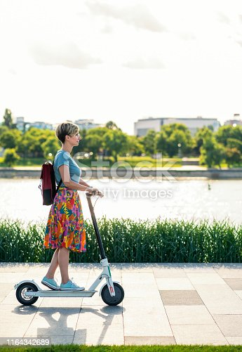 874772840istockphoto Business woman using electric scooter 1164342689