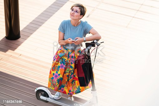 874772840istockphoto Business woman using electric scooter 1164347446