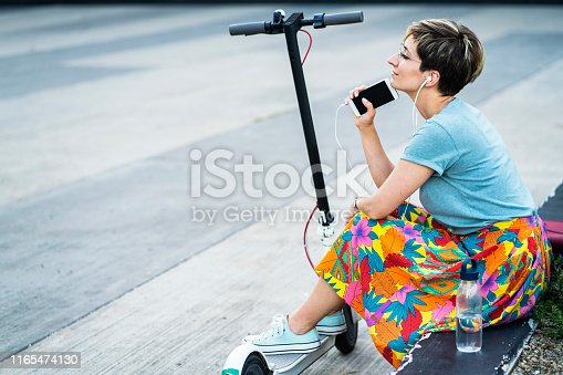 874772840istockphoto Business woman using electric scooter 1165474130