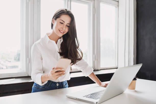 Business woman using laptop and smartphone stock photo