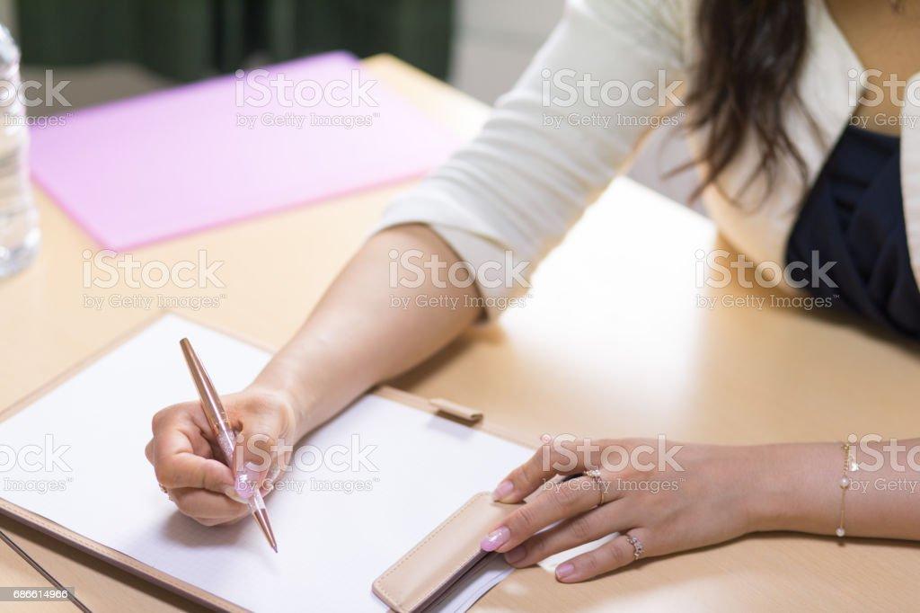 Femme d'affaires à l'aide du stylo et du papier dans la salle de réunion photo libre de droits