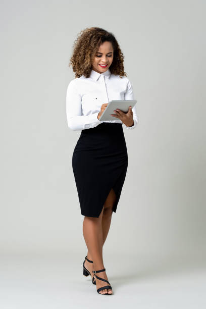 Business woman using tablet computer Smiling African American businesswoman entrepreneur in formal clothing holding digital tablet working against gray background full length stock pictures, royalty-free photos & images